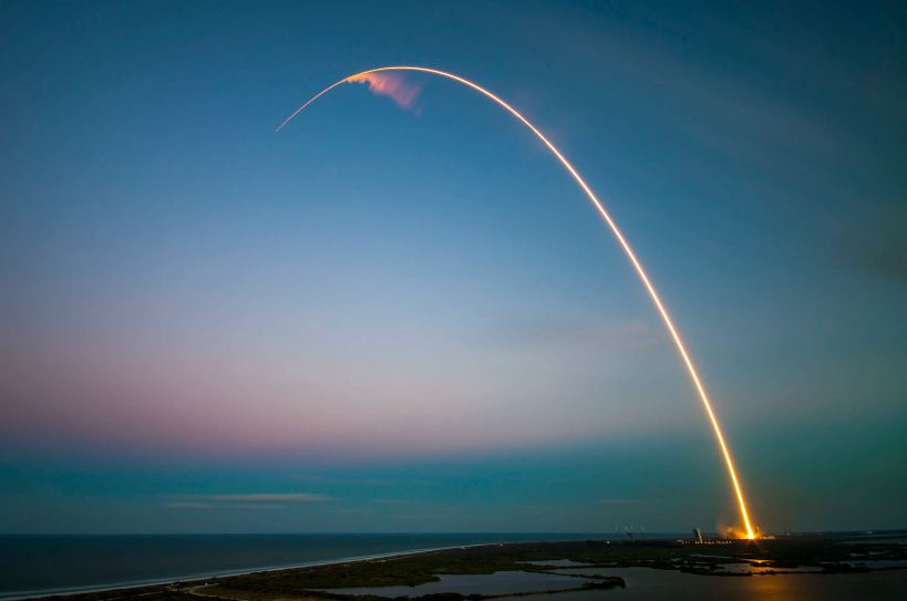 A long exposure shot of the launch of a SpaceX rocket around dusk or dawn.