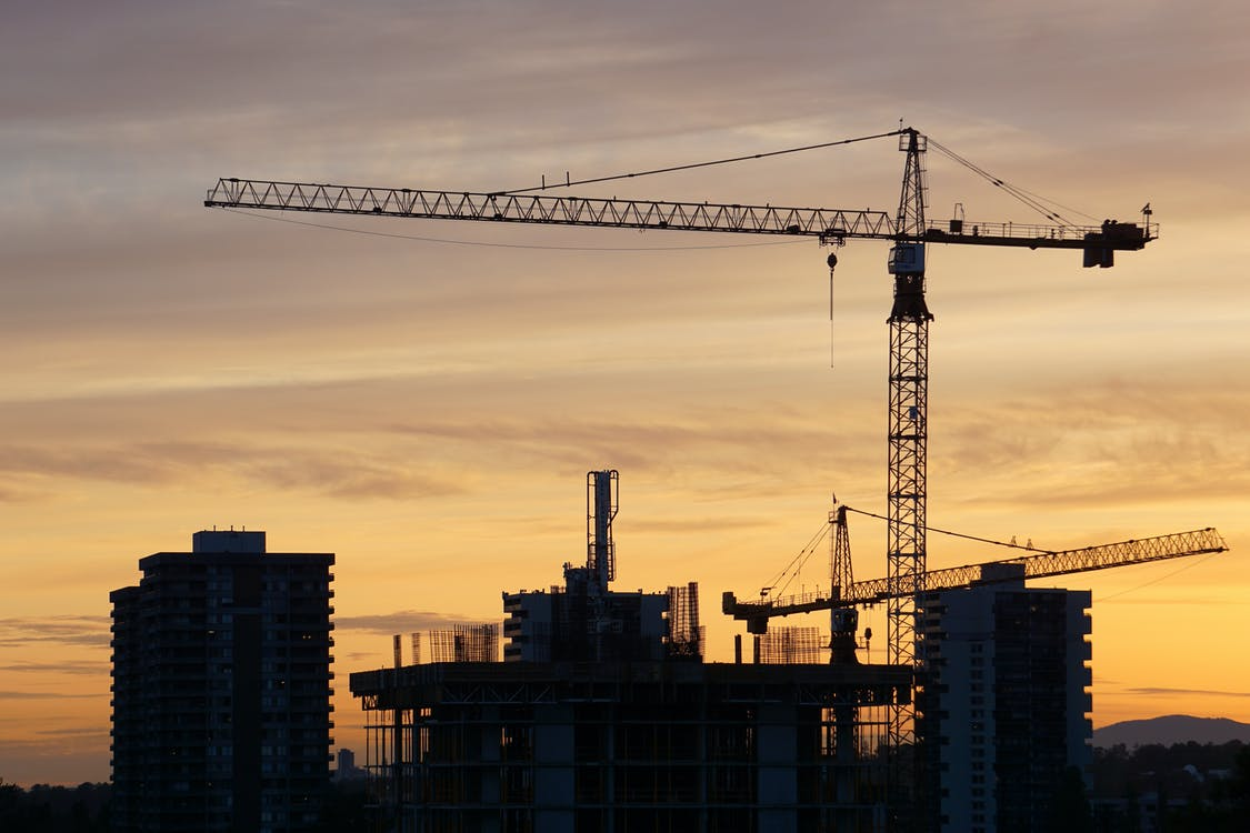 Image showing silhouette of a crane near a high-rise building during sunset.